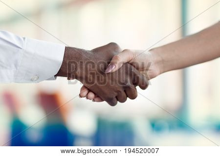 People at work: man and woman hand shaking at a meeting.