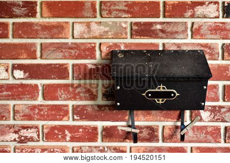 black vintage mailbox on red brick wall