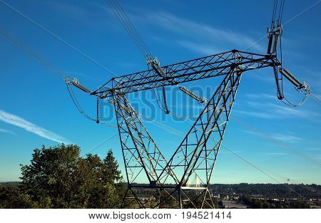 High-voltage support against a blue sky with white clouds