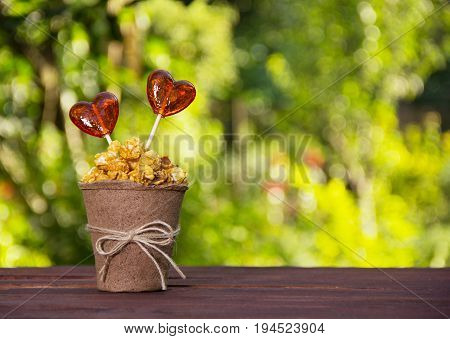 A paper cup with caramel popcorn and candy. Lollipops in the shape of heart. Romantic concept.