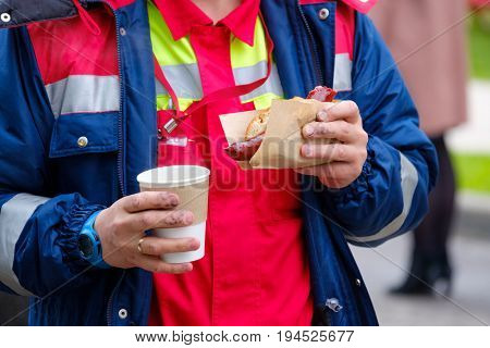 Worker holds hotdog and coffee cup in the dirty hands