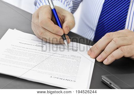Businessman with pen  signing a contract .
