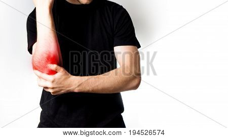 A man in a black T-shirt has his aching elbow on a white background arthritis an old sports injury