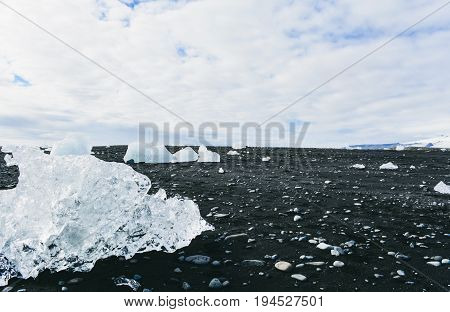 Amazing view of black Iceland beach with diamond ice blocks, Jokulsarlon, Iceland. Global warming and climate change concept.
