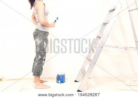 Low section of young woman holding paintbrush in unrenovated house
