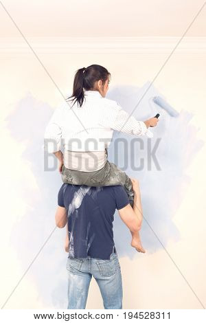 Rear view of man carries woman on his shoulders while painting at home