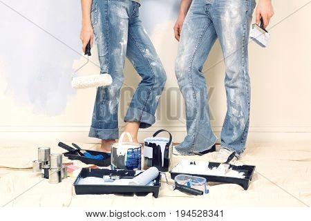 Low section of young couple standing with painting tools in foreground