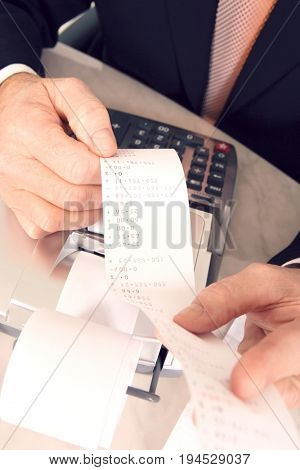 Cropped image of a businessman looking at calculator paper tape