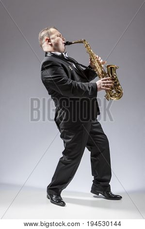 Music Concepts. Full Length Portrait of Caucasian Mature Concentrated Saxophone Player Playing the Instrument Against White Background. Vertical Image Composition