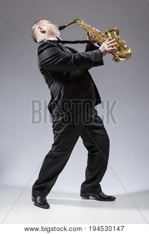 Music Concepts. Full Length Portrait of Caucasian Mature Expressive Saxophone Player Playing the Instrument Against White Background. Vertical Image Composition
