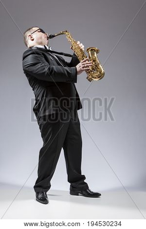 Music Ideas. Full Length Portrait of Caucasian Saxophone Player in Sunglasses Playing the Instrument in Studio Environment. Vertical Composition