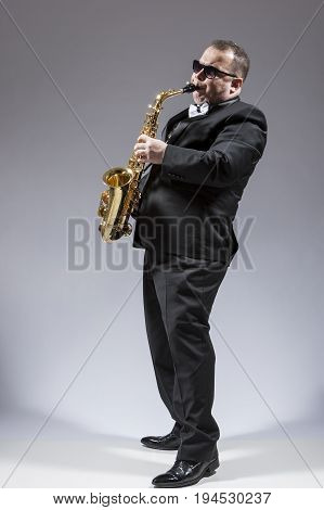 Music Concepts. Full Length Portrait of Mature Expressive Caucasian Saxophone Player in Sunglasses Playing the Saxophone in Studio Environment. Vertical Orientation