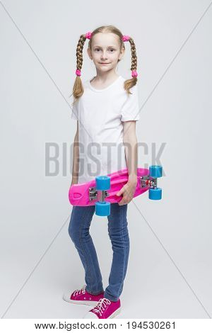 Kids Concepts and Ideas. Full Length Portrait of Little Caucasian Blond Girl with Nice Pigtails Posing With Pink Pennyboard Against White Background. Vertical Shot