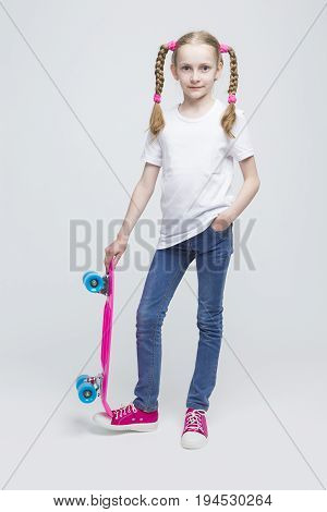 Kids Concepts and Ideas. Full Length Portrait of Little Caucasian Blond Girl with Nice Pigtails Posing With Pink Pennyboard Against White Background. Vertical Image Composition