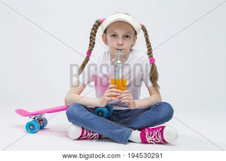 Kid Ideas and Concepts. Portrait of Pretty Caucasian Blond Girl wearing Visor Sitting on Floor with Cup of Juice and Drinking Through Straw. Horizontal Image