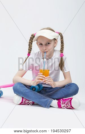 Kid Ideas and Concepts. Portrait of Pretty Caucasian Blond Girl wearing Visor Sitting on Floor with Cup of Juice and Drinking Through Straw.Vertical Shot