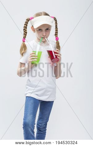 Kids Concepts. Portrait of Little Caucasian Blond Girl in Visor Posing With Two Cups of Juice and Straw. Against White. Vertical Image