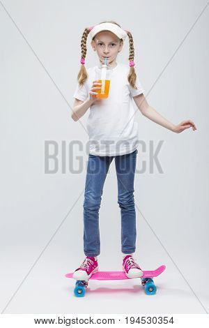 Full Length Portrait of Happy Caucasian Blond Girl in Visor Ballancing on Pennyboard With Cup of Juice.Against White. Vertical Image