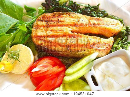 Grilled salmon closeup with fresh salad and lemon