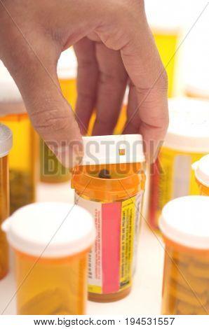 Man's hand opening pill bottle, close-up
