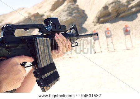 Man aiming machine gun at firing range, close up of hands