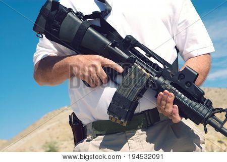 Man holding machine gun at firing range, mid section