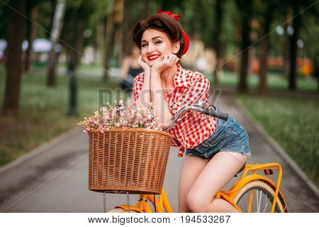 Pinup woman on bicycle with backet of flowers