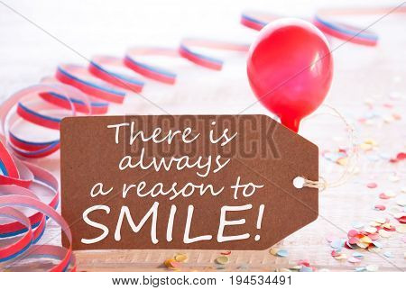 One Label With English Quote There Is Always A Reason To Smile. Party Decoration Like Streamer, Confetti And Balloon. Wooden Background With Vintage, Retro Or Rustic Syle