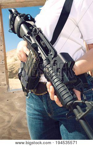 Woman holding machine gun at firing range, mid section