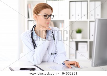 Young brunette female doctor sitting at the table and working by computer  at hospital office.    Doctor is in trouble with diagnosis. Health care, insurance and help concept.