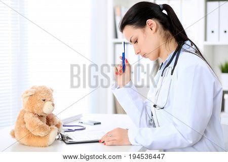Young brunette female doctor sitting at the table and working by computer at hospital office. Doctor is in trouble with diagnosis. Health care, insurance and help concept