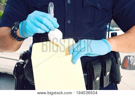 Midsection of a male police officer inserting drug packet in envelope during investigation