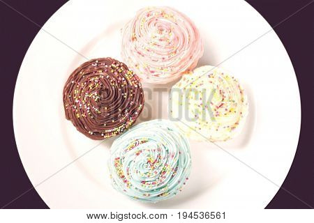 Colourful cupcakes on plate, view from above
