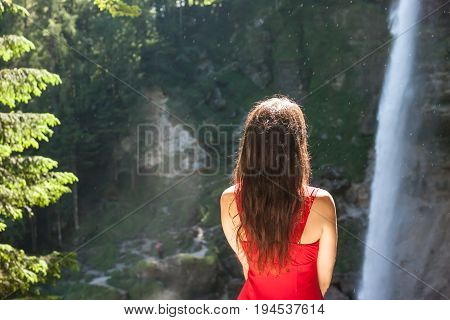 beutiful women in red dress looking at the waterfall