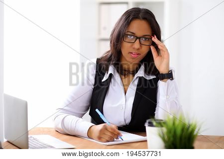 African american business woman is busy with paper job in office while sun shines outdoors