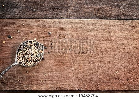 Flatlay image of a tablespoon of pickling spices over a rustic wood plank background. Photo shot from above.