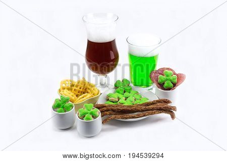 Glass of dark beer glass of green clover plate with appetizers meat chips on white background. St.Patrick 's Day