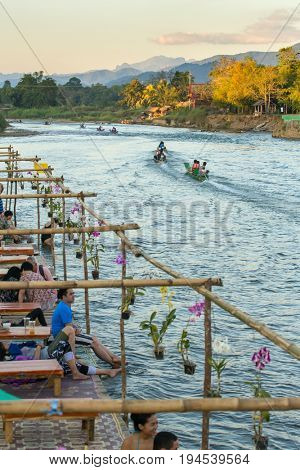 Vang Vieng, Laos - January 19, 2017: Tourists enjoy sunset in river cafe in Vang Vieng village, Laos