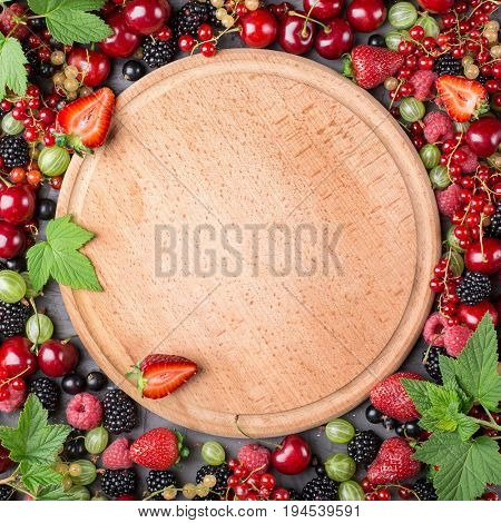 Frame of ripe berries from a garden with leaves on a wooden board. Mix of strawberries, currants, blackberries, cherries. Top view
