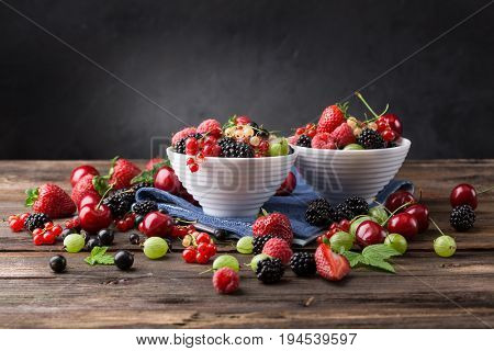 Assorted ripe berries from a garden in a bowl on a wooden board. Mix of strawberries, currants, blackberries, cherries.