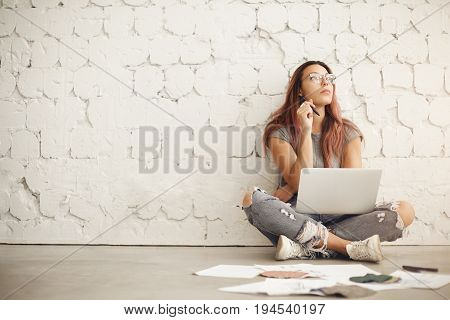 Wide shot of a freelance blog post writer working in a bright studio space sitting in a cafe or a campus surrounded by textile samples and fashion ilustrations