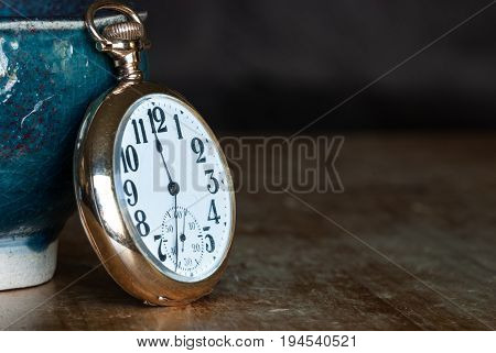 Vintage Golden Pocket Watch Resting on a Wooden Table