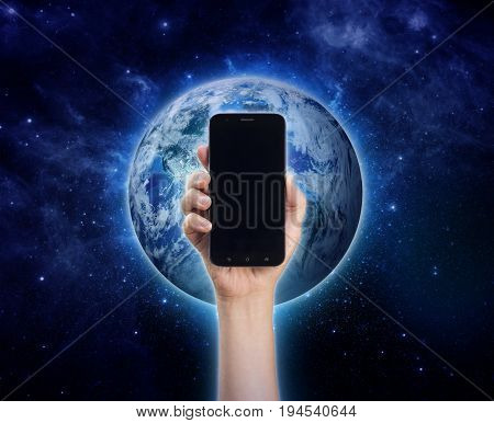 World in hand - hand holding mobile phone or smart phone on Planet Earth background. Life style Technology communication connection Environment Climate issues and Saving the planet concept
