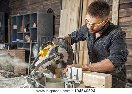 Young brunette man in black overalls by profession carpenter builder saws with a circular saw a wooden board on a wooden table in the workshop