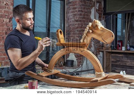 Young brunette man in a dark t-shirt by profession carpenter builder paints a wooden toy in the shape of a horse on a wooden table in the workshop