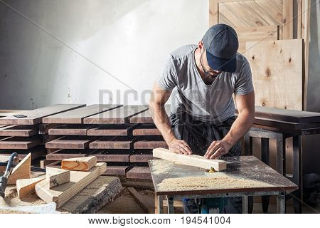 A young man with a cap and a gray T-shirt by profession carpenter builder equals a wooden bar with a milling machine on a wooden table in the workshop around wooden boards