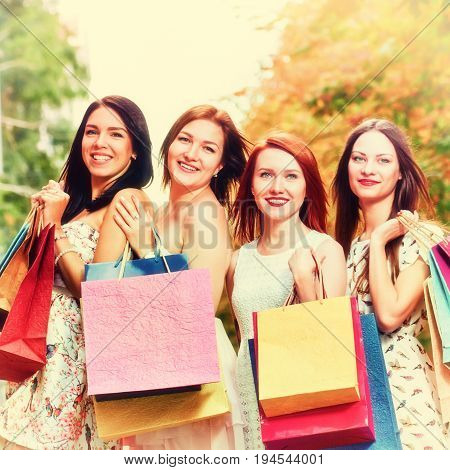 Portrait of four happy girlfriends walking with paperbags after shopping, A picture with toning and a square relation of the sides