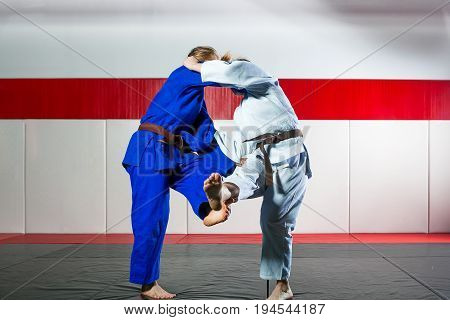 Two young women fight judo on tatami