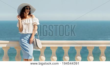 Young woman in a white blouse blue pencil skirt and hat on a background of the sea horizon. Selective focus.