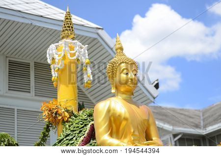 Buddha statue with floral arrange on bright sky background.